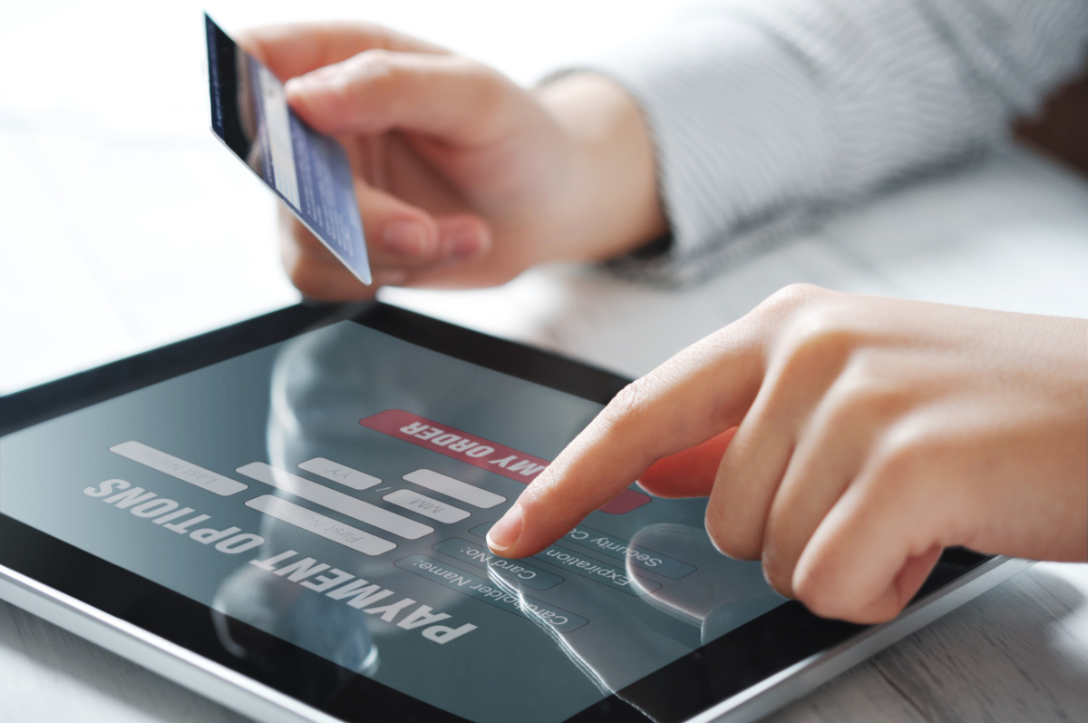A person holding a credit card while making an online transaction on a tablet